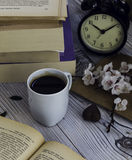 与旧书和闹钟的热的咖啡 免版税图库摄影