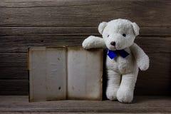 与旧书的玩具熊在木背景,静物画 免版税库存图片