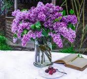 与旧书的美好的丁香构成和花束在花瓶的在白色葡萄酒系带桌布,灰色石墙背景 免版税库存照片