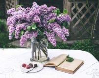 与旧书的美好的丁香构成和花束在花瓶的在白色葡萄酒系带桌布,灰色石墙背景 免版税库存图片