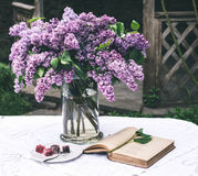 与旧书的美好的丁香构成和花束在花瓶的在白色葡萄酒系带桌布,灰色石墙背景 库存照片