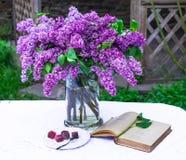 与旧书的美好的丁香构成和花束在花瓶的在白色葡萄酒系带桌布,灰色石墙背景 库存图片