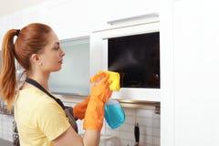 与旧布和洗涤剂的妇女清洗的微波炉 免版税库存照片