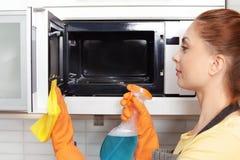 与旧布和洗涤剂的妇女清洗的微波炉 免版税库存图片