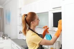 与旧布和洗涤剂的妇女清洗的微波炉 库存照片