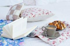与早餐和一本书的静物画在床上 免版税库存图片
