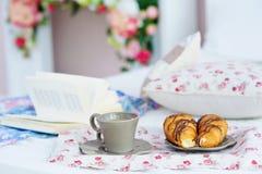 与早餐和书的静物画在床上 免版税库存照片