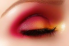 与时尚明亮的构成的特写镜头女性眼睛 美丽的发光的金子,桃红色眼影膏,弄湿了闪烁,黑眼线膏 免版税图库摄影