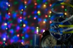 与时钟和圣诞节的两个蜡烛戏弄与在背景的多彩多姿的光 库存图片