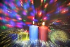 与时钟和圣诞节礼物的两个蜡烛与在背景的多彩多姿的光弄脏了双重焦点图象 图库摄影