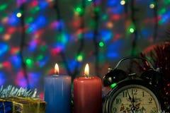 与时钟和圣诞节礼物的两个蜡烛与在背景的多彩多姿的光 库存照片
