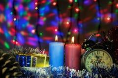 与时钟和圣诞节礼物的两个蜡烛与在背景的多彩多姿的光 免版税库存图片