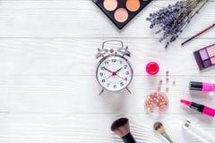 与时钟和淡紫色顶视图嘲笑的化妆用品构成 图库摄影