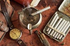 与时钟和香烟的构成在一个减速火箭的样式 库存图片