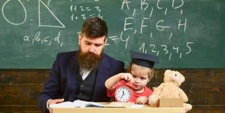 与时钟的乏味孩子戏剧 单独学习的概念 礼服的灰泥板的老师和学生在教室 免版税库存照片