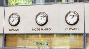 与时钟的劳力士陈列室在有时区的墙壁上 免版税库存照片