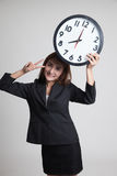 与时钟的年轻亚洲女商人展示胜利标志 免版税库存照片