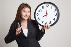 与时钟的年轻亚洲女商人展示胜利标志 免版税图库摄影