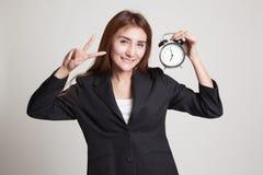 与时钟的年轻亚洲女商人展示胜利标志 库存照片