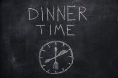 与时钟的晚餐时间文本在黑黑板 库存图片
