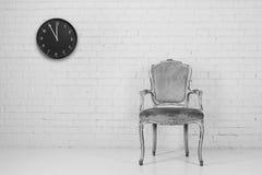 与时钟的老椅子 库存照片