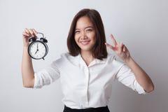 与时钟的年轻亚洲女商人展示胜利标志 库存图片