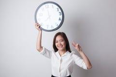 与时钟的年轻亚洲女商人展示胜利标志 免版税库存图片