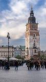 与时髦的大时钟的老塔 城镇厅在克拉科夫,波兰的市中心 前面 图库摄影