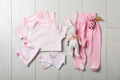 与时髦的婴孩衣裳的平的被放置的构成 免版税库存照片