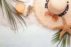 与时髦的帽子和海滩的平的位置构成反对 库存图片