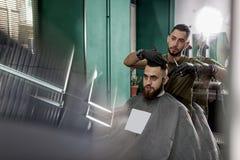 与时髦的有胡子的人的剪刀头发的英俊的理发师裁减理发店的 库存照片