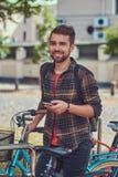 与时髦的理发和胡子,佩带的羊毛衬衣的一个英俊的时兴的年轻男性,在停车场站立为 免版税库存照片