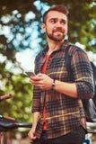 与时髦的理发和胡子,佩带的羊毛衬衣的一个英俊的时兴的年轻男性,在停车场站立为 免版税图库摄影