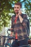 与时髦的理发和胡子,佩带的羊毛衬衣的一个英俊的时兴的年轻男性,在停车场站立为 免版税库存图片