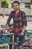 与时髦的理发和胡子,佩带的羊毛衬衣的一个英俊的时兴的年轻男性,在停车场站立为 图库摄影