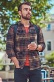 与时髦的理发和胡子,佩带的羊毛衬衣的一个英俊的时兴的年轻男性,在停车场站立为 库存照片