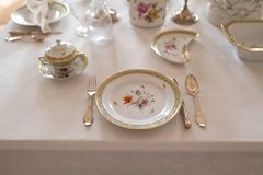与昂贵的减速火箭的皇家雄伟瓷服务板材和利器的婚姻的桌装饰在宫殿 免版税库存图片