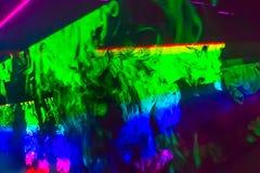 与明亮的五颜六色的光芒和烟的抽象背景 免版税库存图片