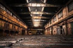 与明亮的光的老被放弃的工业内部 免版税库存照片