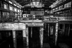 与明亮的光的老被放弃的工业内部 库存图片