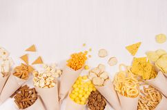 与明亮的嘎吱咬嚼的快餐快餐-烤干酪辣味玉米片,玉米花,油煎方型小面包片,在白色木板,拷贝空间的芯片的米黄纸锥体 库存图片