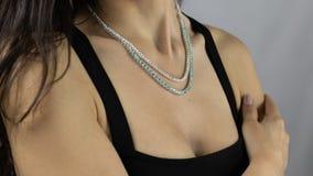 与明亮的宝石的珍贵的项链紧跟在年轻女人后面 免版税库存图片
