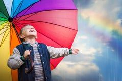 与明亮的彩虹伞的愉快的男孩画象 免版税图库摄影
