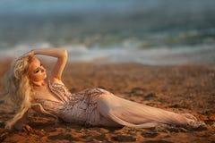 与明亮的户外构成正在流行的样式的白肤金发的少妇模型在蓝天后的晚礼服 免版税图库摄影