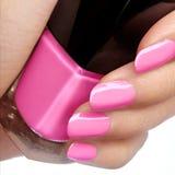 与明亮的指甲油的被修剪的钉子 与桃红色nailpolish的修指甲 时尚修指甲 在瓶的发光的胶凝体亮漆 图库摄影