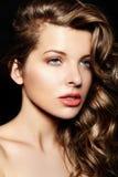 与明亮的构成的性感的时髦的深色的白种人少妇模型,与有蓝眼睛大嘴唇的卷曲healty头发在演播室 免版税库存图片