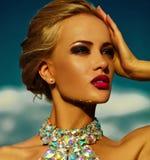 与明亮的构成的性感的时髦的白肤金发的模型在晚礼服 免版税库存图片