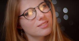 与明亮的构成的白肤金发的模型在诱人地微笑入在bokeh背景的照相机的镜片 股票视频