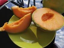 与明亮的橙色骨肉的成熟切的甜瓜 免版税库存照片