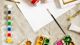 与明亮的油漆在小圆的容器和许多调色板,刷子和白色纸片的Flatlay在灰色水泥backcground的 库存照片